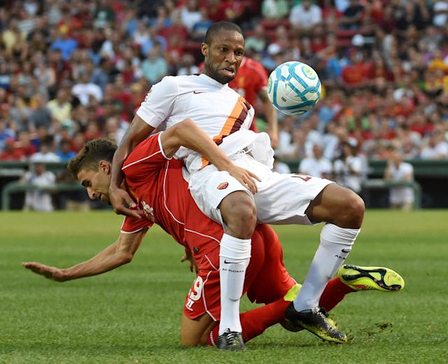 Liverpool's Fabio Borini (L) tussles with Roma's Seydou Keita during a friendly soccer match between Liverpool and Roma at Fenway Park, Boston on July 23, 2014 (AFP Photo/Dominick Reuter)