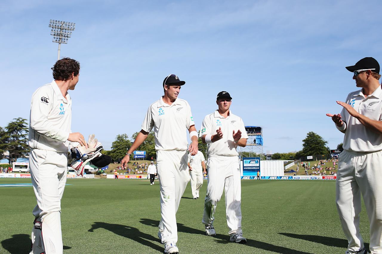 HAMILTON, NEW ZEALAND - DECEMBER 21:  Tim Southee of New Zealand is congratulated by the team after claiming his 100th test wicket during day three of the Third Test match between New Zealand and the West Indies at Seddon Park on December 21, 2013 in Hamilton, New Zealand.  (Photo by Hannah Johnston/Getty Images)