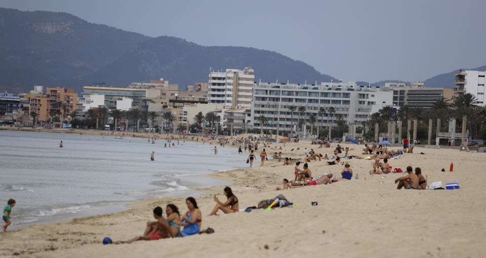 25 May 2020, Spain, Palma de Mallorca: People sunbathe on the beach of Arenal. After more than two months of forced closure due to the Corona pandemic, the holiday island and many other regions of Spain reopened their beaches on Monday. Photo: Clara Margais/dpa (Photo by Clara Margais/picture alliance via Getty Images)