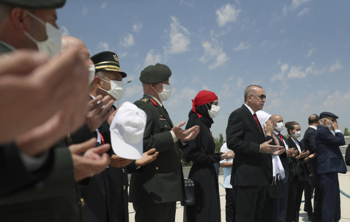 """Turkey's President Recep Tayyip Erdogan, center, and family members of coup victims pray at the """"Martyrs Monument"""" outside his presidential palace, in Ankara, Turkey, Wednesday, July 15, 2020. Turkey is marking the fourth anniversary of the July 15 failed coup attempt against the government, with prayers and other events remembering its victims.(Turkish Presidency via AP, Pool)"""