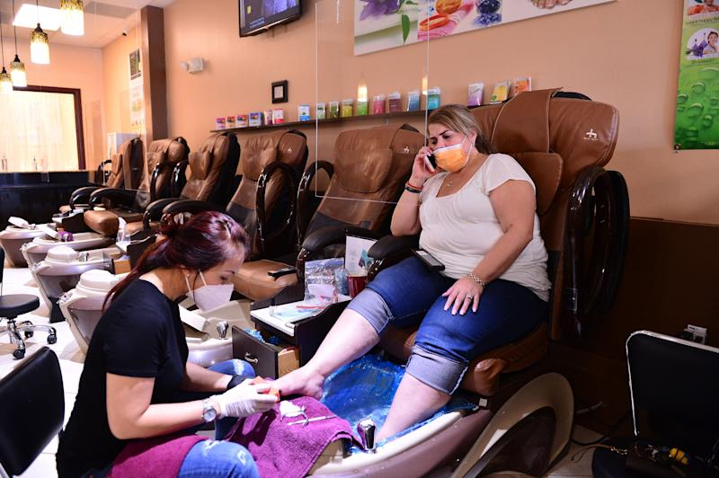 Nail technician Jimmie and her customer wear masks during a pedicure at Nails and Spa salon on May 20, 2020, in Miramar, Florida. (Photo: Johnny Louis via Getty Images)
