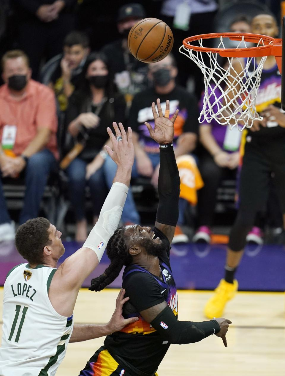 Phoenix Suns forward Jae Crowder, right, gets off a shot as Milwaukee Bucks center Brook Lopez (11) defends during the second half of Game 1 of basketball's NBA Finals, Tuesday, July 6, 2021, in Phoenix. (AP Photo/Ross D. Franklin)