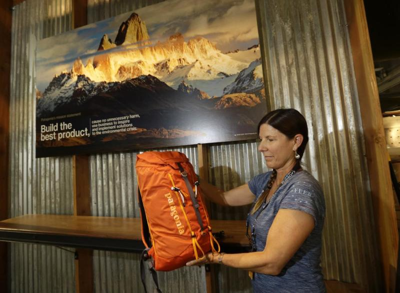 """Tania Bjornlie, from Patagonia, holds one of the new Patagonia day packs a during set up at the Outdoor Retailer Summer Market Tuesday, July 30, 2013, in Salt Lake City. The Outdoor Retailer Summer Market opens for a four-day run Wednesday. More than 1,300 manufacturers and suppliers are packing every square inch of the floor of a Salt Lake City convention hall. """"The industry is doing well. Patagonia has weathered the storm,"""" said Bjornlie, a trade-show manager for the Ventura, Calif.-based industry giant long known for its sleek outdoor clothing. Patagonia is now showing off a new line of day packs. """"Everything at the show is getting more technical, lighter, faster,"""" Bjornlie said. (AP Photo/Rick Bowmer)"""