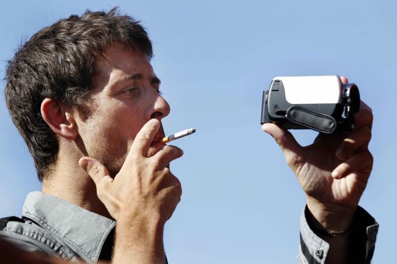 French Journalist Romeo Langlois smokes as he films after being released in San Isidro, southern Colombia, Wednesday, May 30, 2012. French journalist Romeo Langlois , who was taken by rebels on April 28 when they attacked troops he was accompanying on a cocaine-lab eradication mission, was handed over by the rebels to a delegation that included a French diplomat in San Isidro. (AP Photo/Fernando Vergara)