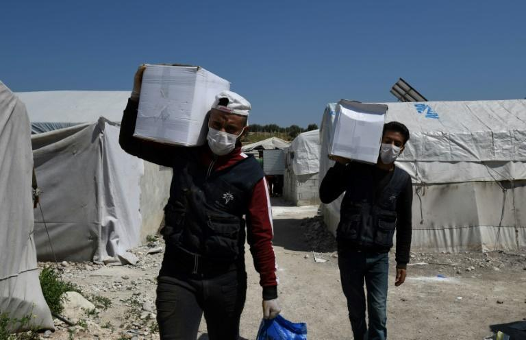 Volunteers deliver aid at a camp for displaced Syrians near the town of Deir al-Ballut in Aleppo province, by the border with Turkey in April 2020