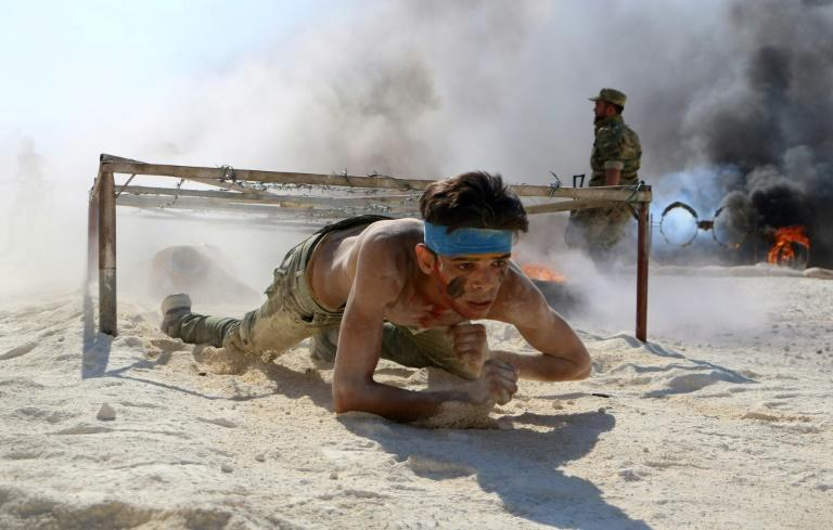 A Syrian rebel fighter from the National Liberation Front receives military training in the northern countryside of Idlib province on September 1, 2018