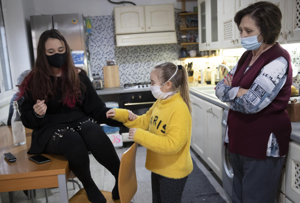 Rita Cintio, 76, wears a face mask to curb the spread of COVID-19 as she looks at her nieces Gaia, center and Elisa, while visiting them at her son's house, in Rome, Wednesday, Dec. 16, 2020. In Italy, which has the world's second-oldest population, many people in their 70s and older have kept working through the COVID-19 pandemic. From neighborhood newsstand dealers to farmers bring crops to market, they are defying stereotypic labels that depict the old as a monolithic category that's fragile and in need of protection. (AP Photo/Alessandra Tarantino)