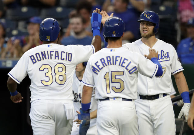 Kansas City Royals' Hunter Dozier, right, congratulates teammates Jorge Bonifacio (38) and Whit Merrifield (15) during the first inning of a baseball game against the Minnesota Twins at Kauffman Stadium in Kansas City, Mo., Friday, July 20, 2018. Bonifacio and Merrifield scored on a bloop single by Lucas Duda. (AP Photo/Orlin Wagner)
