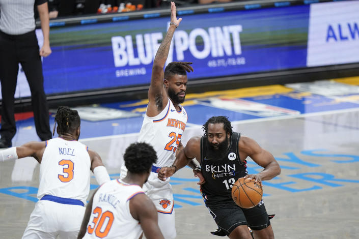 Brooklyn Nets' James Harden (13) drives past New York Knicks' Reggie Bullock (25) during the first half of an NBA basketball game Monday, April 5, 2021, in New York. (AP Photo/Frank Franklin II)
