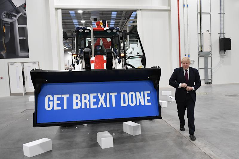"Prime Minister Boris Johnson walks away after driving a Union flag-themed JCB, with the words ""Get Brexit Done"" inside the digger bucket, through a fake wall emblazoned with the word ""Gridlock"", during a visit to JCB cab manufacturing centre in Uttoxeter, while on the General Election campaign trail."