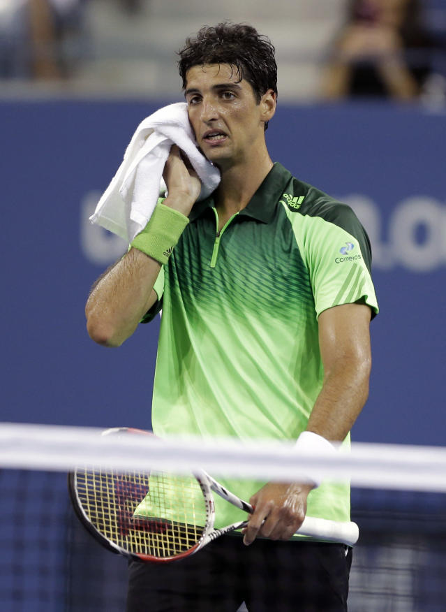 Thomaz Bellucci, of Brazil, wipes his faces after having his serve broken during a match against Stan Wawrinka, of Switzerland, during the second round of the U.S. Open tennis tournament Wednesday, Aug. 27, 2014, in New York. (AP Photo/Darron Cummings)