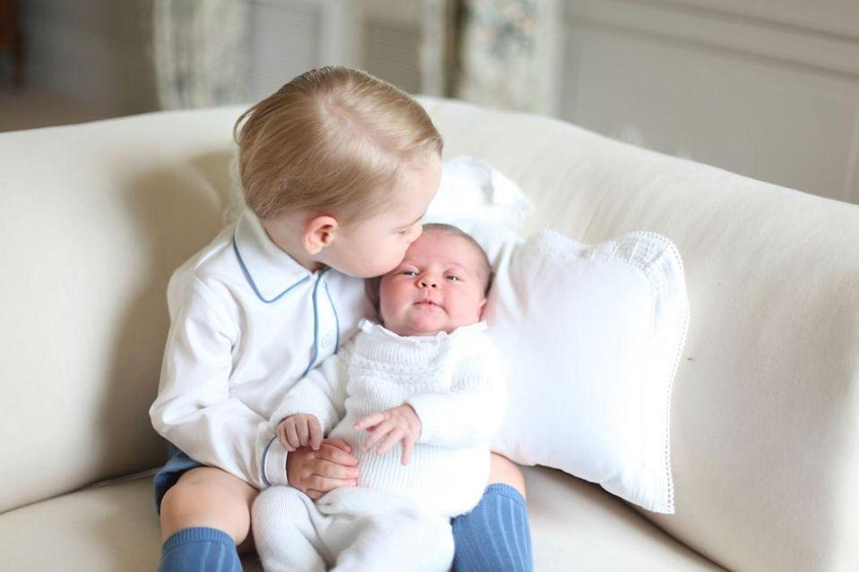 <p>Prince George gives his new baby sister a kiss on the forehead in this portrait of the siblings released shortly after Princess Charlotte's birth in 2015. </p>