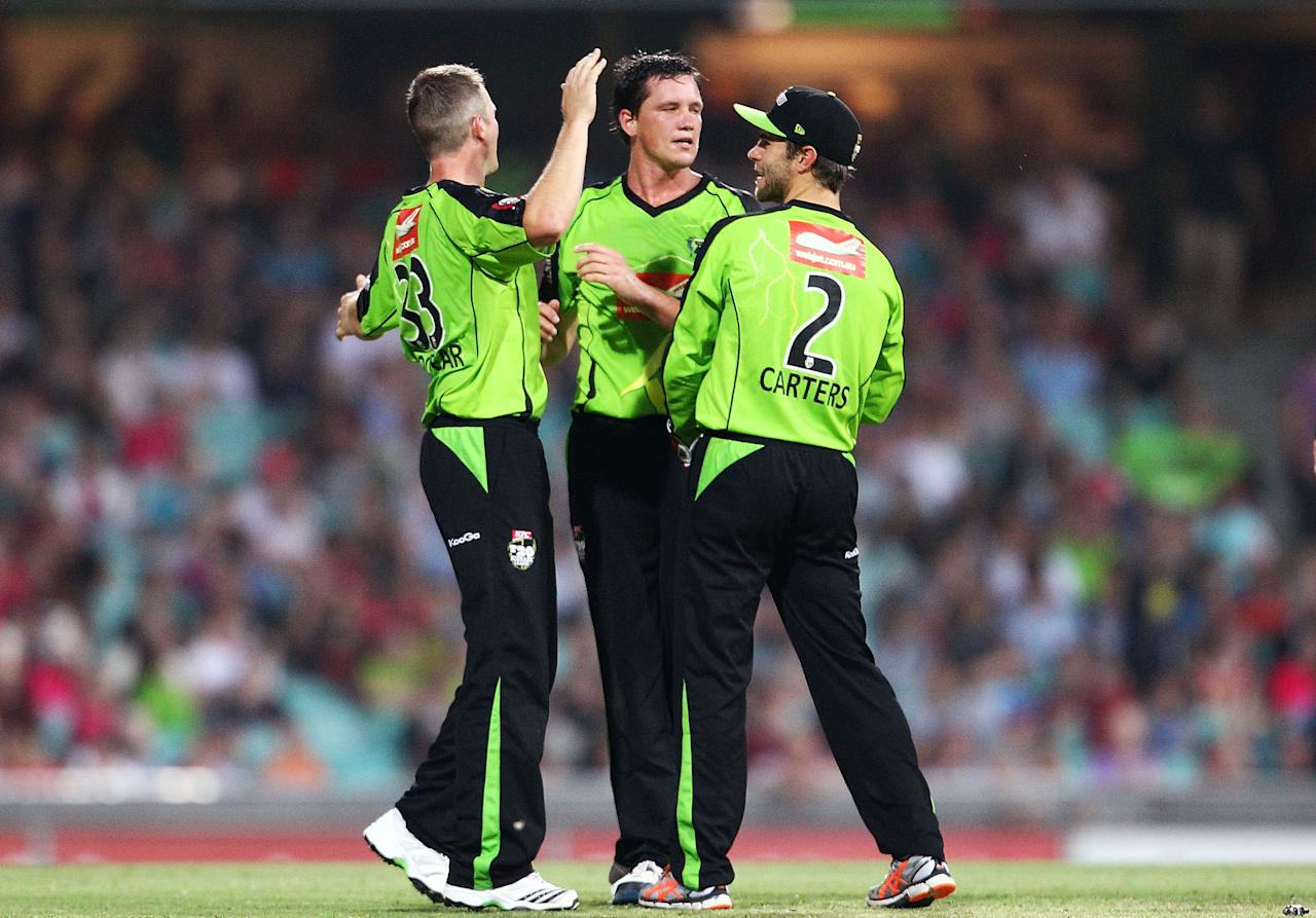 SYDNEY, AUSTRALIA - DECEMBER 08:  Chris Tremain (C) of the Thunder celebrates with team mates after getting the wicket of Nic Maddinson of the Sixers during the Big Bash League match between the Sydney Sixers and the Sydney Thunder at Sydney Cricket Ground on December 8, 2012 in Sydney, Australia.  (Photo by Mark Nolan/Getty Images)