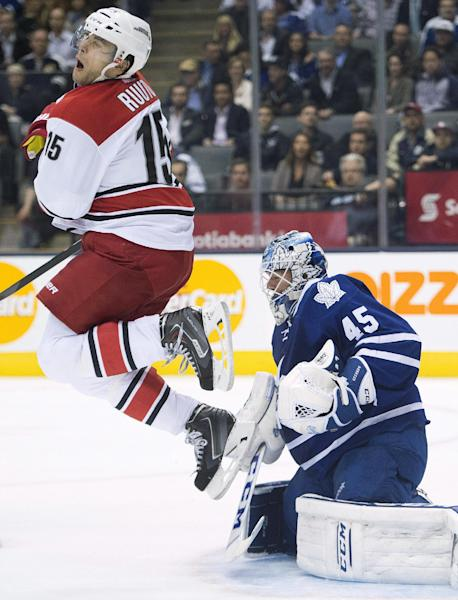Toronto Maple Leafs goalie Jonathan Bernier, right, makes a save on a tip from Carolina Hurricanes forward Tuomo Ruutu, left, during the first period of an NHL hockey game in Toronto on Thursday, Oct. 17, 2013. (AP Photo/The Canadian Press, Nathan Denette)