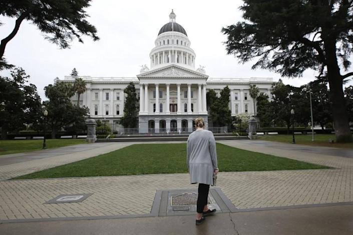 """FILE - In this March 18, 2020, file photo, a woman pauses to look at the historical marker about the state Capitol in Sacramento, Calif. A veteran employee at the California state Capitol has died after contracting the coronavirus. Lawrence """"Larry"""" Luna III died on Dec. 22, 2020, after a battle with COVID-19, according to a memo from Secretary of the Senate Erika Contreras. The 58-year-old was the automotive pool manager for the Department of General Services at the Capitol garage. (AP Photo/Rich Pedroncelli, File)"""