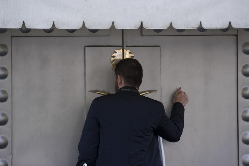 "A man knocks the entrance of the Saudi Arabia's consulate in Istanbul, Friday, Oct. 12, 2018. A senior Turkish official says Turkey and Saudi Arabia will form a ""joint working group"" to look into the disappearance of Saudi writer Jamal Khashoggi. (AP Photo/Petros Giannakouris)"