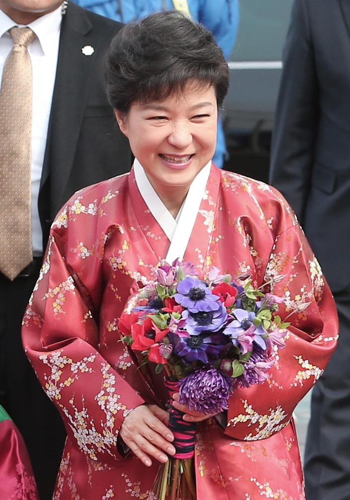 South Korea's new President Park Geun-hye wearing a traditional dress smiles upon arriving at the presidential house after her inauguration ceremony as the 18th South Korean president in Seoul, South Korea, Monday, Feb. 25, 2013. Park took office as South Korea's first female president Monday, returning to the presidential mansion she had known as the daughter of a dictator, and where she will respond to volatile North Korea, which tested a nuclear device two weeks ago. (AP Photo/Yonhap, Suh Myung-gon) KOREA OUT