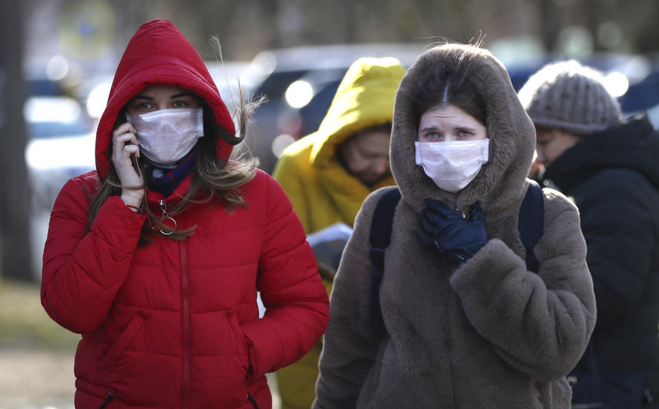 People wearing masks, walk on street in Minsk, Belarus, Friday, Feb. 28, 2020. Belarus, Lithuania and New Zealand have reported their first cases of coronavirus. (AP Photo/Sergei Grits)