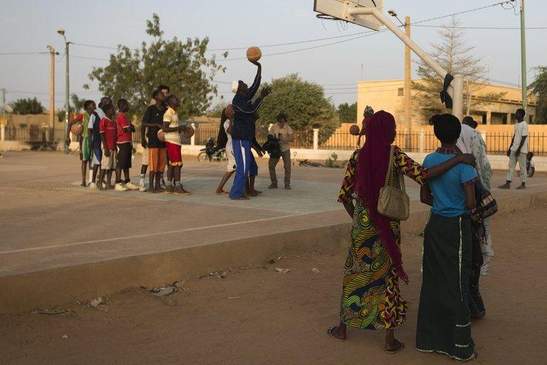 """Local youngsters are seen playing basketball at the former """"Sharia Square"""" in central Gao, on February 26, 2013. Since the departure of the Islamists, who occupied the city for nine months, following the arrival of the French and Malian forces, the central square of Gao is once again called """"Independence square."""""""