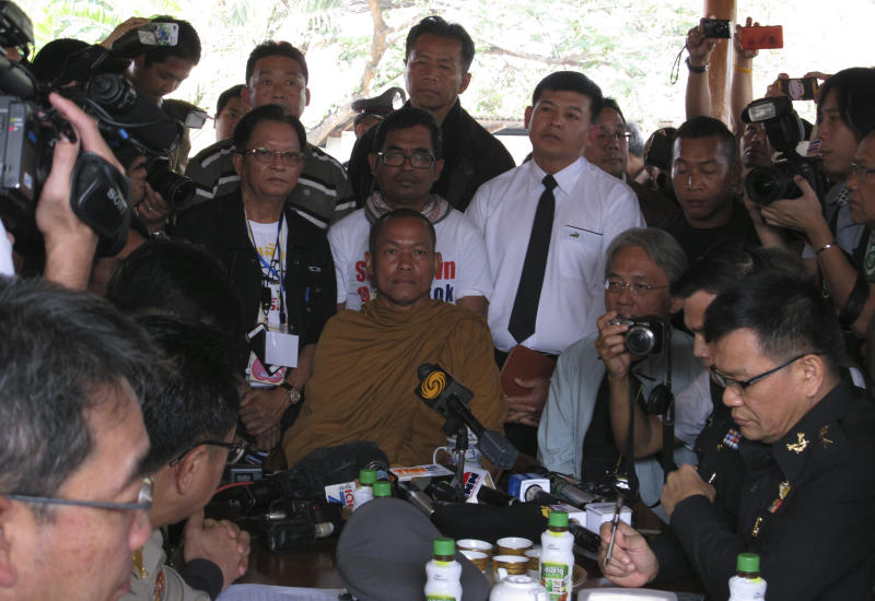 In this photo taken Monday, Jan. 27, 2014, local monk protest leader Luang Pu Buddha Issara, center, listens to high level police officers asking him to leave the neighboring government building to Bangkok, Thailand. Some government officials have resorted to pleading with protests occupying their government offices where daily functions such as passport controls and immigration issues are backing up. It was an extraordinarily humbling moment for Prime Minister Yingluck Shinawatra's embattled administration, which ascended to power following a landslide election two and a half years ago. (AP Photo/Thanyarat Doksone)