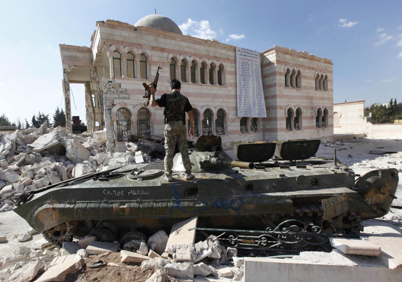 FILE - In this Sept. 23, 2012, file photo, a Free Syrian Army soldier stands on a damaged Syrian military tank in front of a damaged mosque, which were destroyed during fighting with government forces, in the Syrian town of Azaz, on the outskirts of Aleppo. Al-Qaida-linked gunmen in northern Syria captured a town near the Turkish border Thursday, Sept. 19, 2013, following heavy clashes with mainstream, Western-backed rebels in the area, prompting Turkey to close a nearby crossing, activists and Turkish officials said. (AP Photo/Hussein Malla, File)