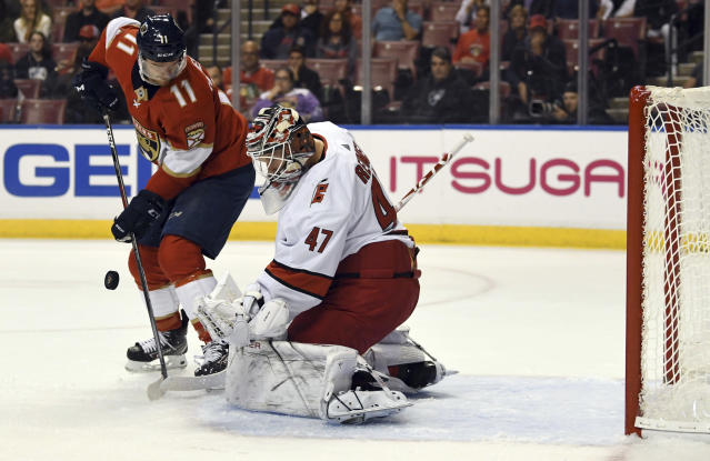 Carolina Hurricanes goaltender James Reimer (47) blocks a shot by Florida Panthers center Jonathan Huberdeau (11) during the first period of an NHL hockey game Tuesday, Oct. 8, 2019, in Sunrise, Fla. (AP Photo/Jim Rassol)