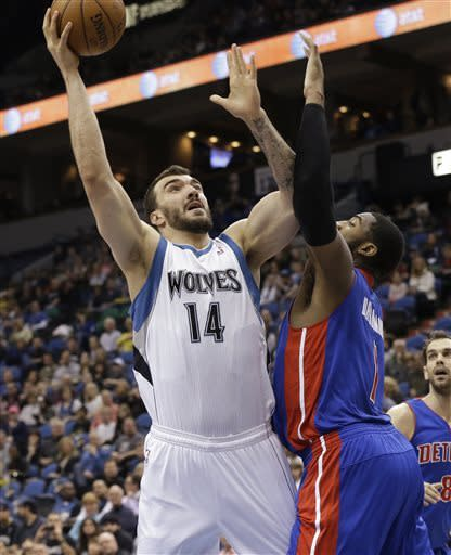 Minnesota Timberwolves' Nikola Pekovic (14), of Montenegro, lays up a shot as Detroit Pistons' Brandon Knight defends in the first quarter of an NBA basketball game, Saturday, April 6, 2013, in Minneapolis. (AP Photo/Jim Mone)