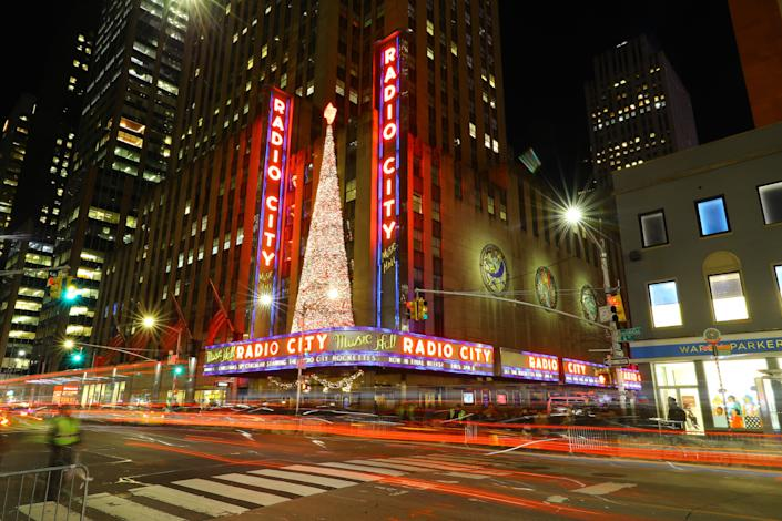 A Christmas tree made of lights shines on the marquee of Radio City Music Hall as traffic streaks moves up Sixth Ave. (Photo: Gordon Donovan/Yahoo News)