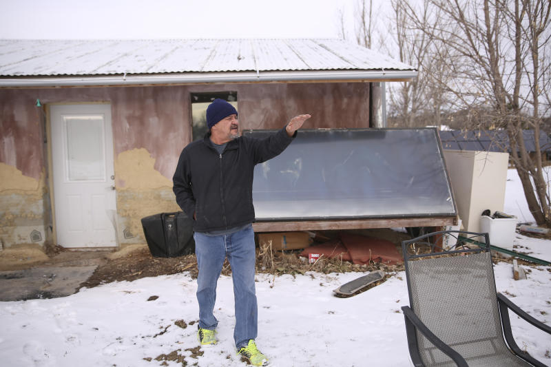 In this Dec. 11, 2019 photo, Henry Red Cloud points to his property where flooding rose as high as 3-feet in March on the Pine Ridge Indian Reservation in South Dakota. He fears what winter storms will do after flooding damaged their home last spring. They ran workshops on solar panel and wind turbine installation, but had to halt the classes when flooding damaged their tools and property. (AP Photo/Stephen Groves)
