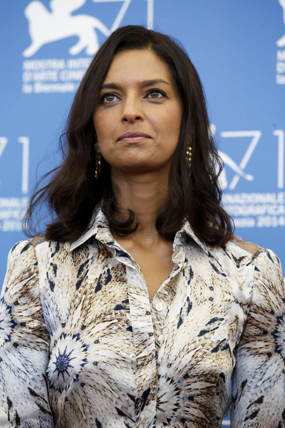"""FILE - Jhumpa Lahiri poses during a photo call at the 71st edition of the Venice Film Festival in Venice, Italy, on Aug. 27, 2014. Princeton University Press announced Monday that Lahiri's """"Translating Myself and Others"""" will come out in May. (AP Photo/Andrew Medichini, File)"""