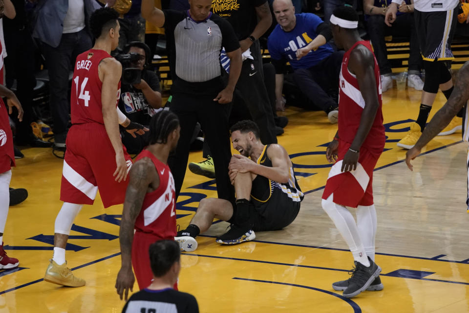 Golden State Warriors guard Klay Thompson, center, reacts after being injured during the second half of Game 6 of basketball's NBA Finals against the Toronto Raptors in Oakland, Calif., Thursday, June 13, 2019. (AP Photo/Tony Avelar)