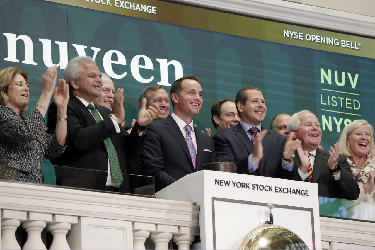 Nuveen Sr. Vice President & Portfolio Manager Daniel Close, third left, is applauded as he rings the New York Stock Exchange opening bell, Tuesday, June 27, 2017. (AP Photo/Richard Drew)