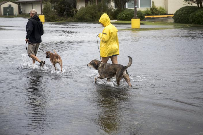 Pedestrians cross a flooded parking lot after Hurricane Florence in Wilmington, North Carolina, U.S., on Saturday, Sept. 15, 2018.