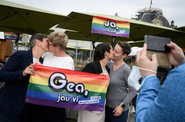 Supporters of same-sex marriage kiss after learning that nearly two-thirds of Swiss voters cast their ballots in favour of legalisation (AFP/Fabrice COFFRINI)