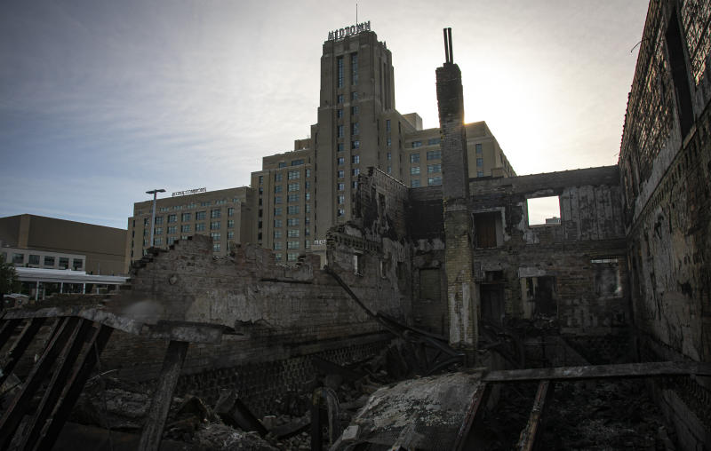 A former Sears building, now known as the Midtown Market place, stands behind buildings destroyed in a fire from riots Sunday May 31, 2020, in Minneapolis. Outrage following the death of George Floyd, who died after being restrained by Minneapolis police officers on May 25, has led to the burning of businesses along the Lake Street corridor where immigrants have found success. (AP Photo/Bebeto Matthews)