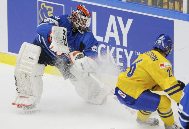Finland's goalie Juuse Saros (L) comes out to play the puck against Sweden's Erik Karlsson during the second period of their IIHF World Junior Championship gold medal ice hockey game in Malmo, Sweden, January 5, 2014. REUTERS/Alexander Demianchuk (SWEDEN - Tags: SPORT ICE HOCKEY)