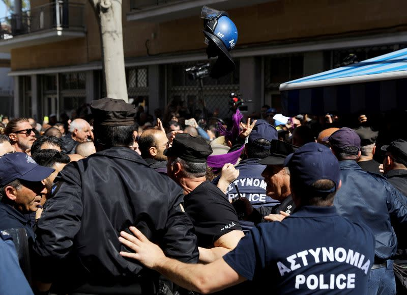 Turkish Cypriots scuffle with  Greek Cypriot policemen at Ledra's checkpoint of the U.N.-controlled buffer zone, after authorities declared the crossing temporarily shut to curb any potential spread of coronavirus,