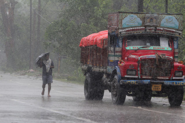 A man walks in the rain ahead of Cyclone Amphan landfall, at Bhadrak district, in the eastern Indian state of Orissa, Wednesday, May 20, 2020. A strong cyclone blew heavy rains and strong winds into coastal India and Bangladesh on Wednesday after more than 2.6 million people were moved to shelters in a frantic evacuation made more challenging by coronavirus. (AP Photo)