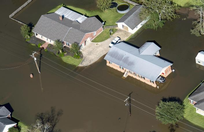 FILE - In this Oct. 10, 2020 file photo, houses surrounded by flood waters are seen in the aftermath of Hurricane Delta Saturday in Welsh, La. Hurricane Delta, which made landfall about 11 miles from where the devastating Hurricane Laura hit a little more than a month earlier, cost $2.9 billion in the United States and was linked to six deaths in the U.S. and Mexico, according to a report from the National Hurricane Center. (Bill Feig/The Advocate via AP, Pool, File)
