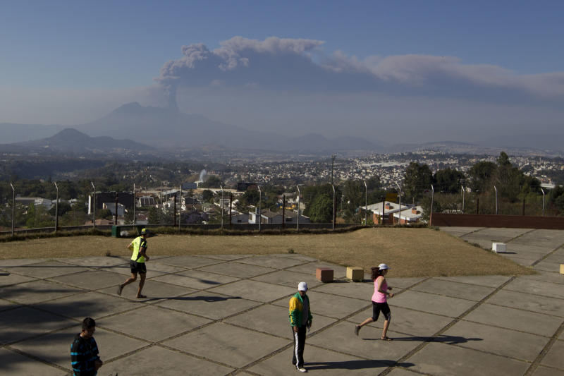 Residents exercise as a column of ash rises from the Pacaya volcano in Villa Nueva, Guatemala, Sunday, March 2, 2014. Guatemala authorities say the Pacaya volcano near Guatemala City has shot plumes of ash and vapor 2.3 miles (3.7 kilometers) high, while spewing glowing-hot rock. The eruption early Sunday is the latest round of activity at the scenic volcano located just 30 miles (50 kms) south of Guatemala City. (AP Photo/Moises Castillo)