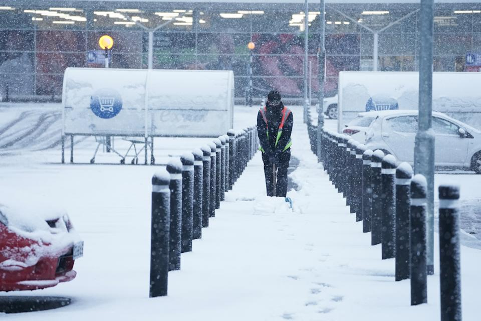 A member of staff from Tesco Extra shovels snow outside the store in Hexham, Northumberland. Heavy snow and freezing rain is set to batter the UK this week, with warnings issued over potential power cuts and travel delays. (Photo by Owen Humphreys/PA Images via Getty Images)