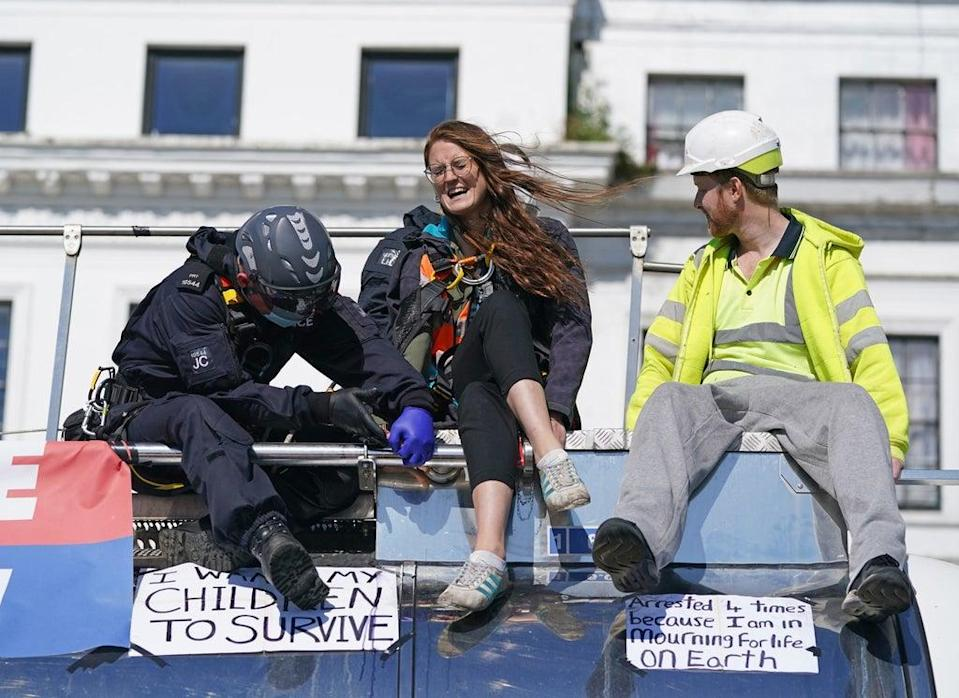 Police officers remove two protesters from the top of a tanker (PA)