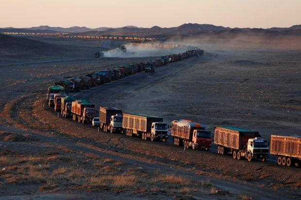 A snaking line of coal trucks heading from Mongolia to China, where it is estimated more than 60 percent of power comes from cheap and plentiful coal and giving Chinese industry a carbon price advantage.
