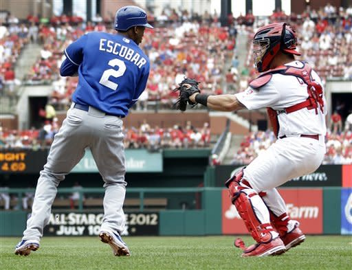 Kansas City Royals' Alcides Escobar, left, is tagged out by St. Louis Cardinals catcher Tony Cruz after being caught between third and home during the second inning of a baseball game on Sunday, June 17, 2012, in St. Louis. (AP Photo/Jeff Roberson)
