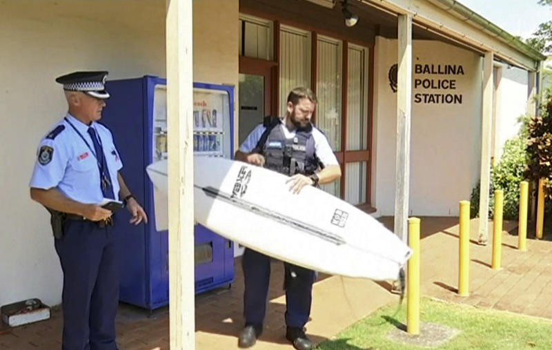 In this Nov. 7, 2018, image made from video police holds a victim's surfboard at a police station in Ballina, Australia. A man has used his surfboard to fend off a shark that bit him on his calf off an Australian beach two days after a fatal attack on the Great Barrier Reef. The 43-year-old surfer was bitten Wednesday morning, Nov. 7, at Shelly Beach off Ballina in New South Wales state. (Australian Broadcasting Corporation via AP)