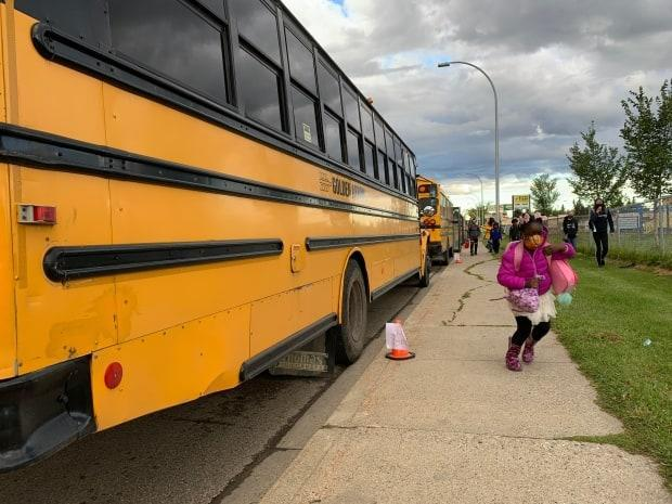 A masked student disembarks her bus and heads off to her first day of school in Edmonton. (Dave Bajer/CBC - image credit)