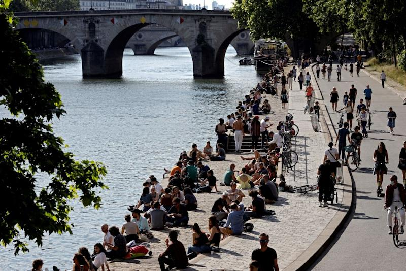 People gather and take a sun bath on the banks of the river Seine in Paris, on May 19, 2020. Source: Getty