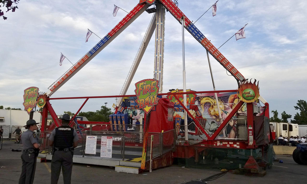 <p>Authorities stand near the Fire Ball amusement ride after the ride malfunctioned injuring several at the Ohio State Fair, Wednesday, July 26, 2017, in Columbus, Ohio. Some of the victims were thrown from the ride when it malfunctioned Wednesday night, said Columbus Battalion Chief Steve Martin. (Jim Woods/The Columbus Dispatch via AP) </p>
