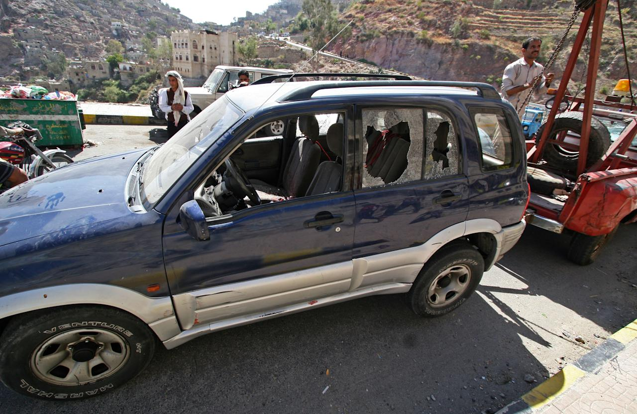 A damaged vehicle purported to belong to an American teacher shot by gunmen is towed away in Taiz, Yemen, Sunday, March 18, 2012. Two gunmen on a motorcycle shot dead early Sunday an American teacher working at a language institute in a central Yemeni city, the region's provincial governor said. (AP Photo/Anees Mahyoub)
