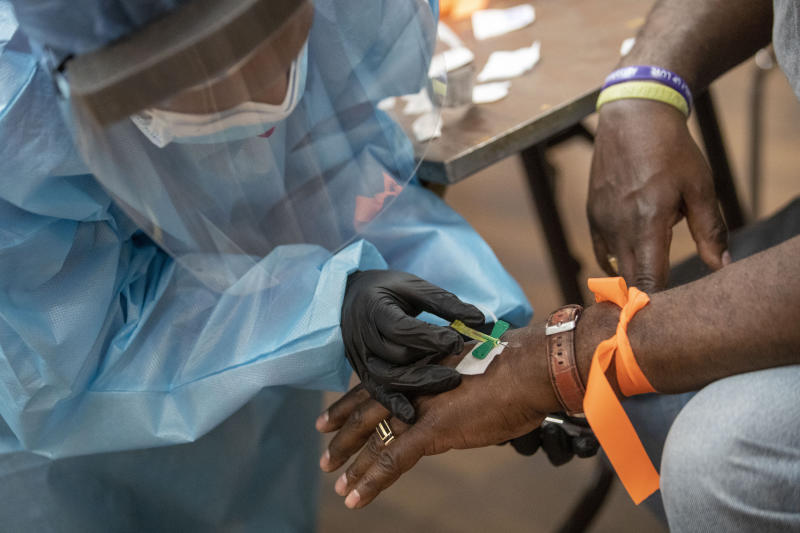 A registered nurse draws blood during a COVID-19 antibody test drive at the Abyssinian Baptist Church, Thursday, May 14, 2020, in the Harlem neighborhood of the Manhattan. Churches in low income communities across New York are offering COVID-19 testing to residents in conjunction with Northwell Health and New York State. (AP Photo/Mary Altaffer)